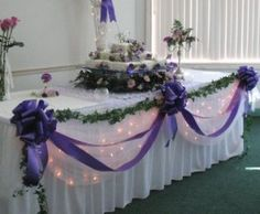 purple ribbons and bows paired with draped tulle, green floral garland and strands of white lights. Idea for cake table or escort card table or gift table or bridal party table. Would also be possible idea for guest book table at wedding ceremony