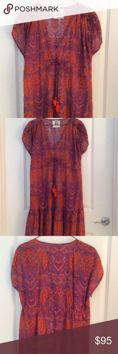 """Orange + Purple Batik Tassel Dress Perfect sundress for summer! Orange and purple with empire drawstring waist and tassels. Slight baby doll ruffle styling at hem. Ruched tie sleeves. V-Neck. 100% Cotton. New without tags. Bust {up to 42"""".} Length {37"""".} Fourth photo shows same print on fashion blogger, With Love From Kat {so it's an awesome must-have print!} Figue Dresses"""