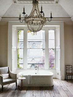 Incredible bathroom with large scale crystal beaded candelabra chandelier hung from a plastered tray ceiling with molding border over freestanding marble tub with floor mount faucet. The tub stands in front of a traditional bay window with a linen arm chair and small wooden side table to the left over unfinished hardwood floors.