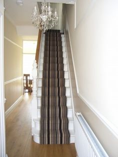 Striped stair runner with engineered oak hall flooring offer a welcome view to visitors in this Victorian house.
