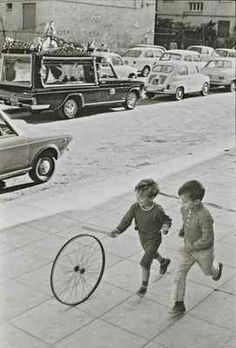 Black and white photo | Little boys playing, rolling a wheel down the street | Vintage