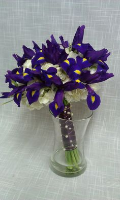 Deep purple iris tucked in a bed of white hydrangea with a satin stem wrap and ivory pearl embellishments.