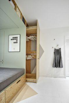 Мятный интерьер. Сочетание светло-зеленого, черного, белого и дерева. Кровать на подиуме. В стены встроены полки и шкафы.