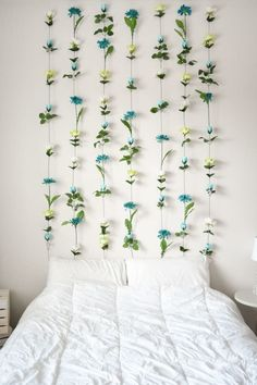 Cut flowers off a plastic bouquet, and glue the stems to the buds. Tie fishing wire around the top flowers and hang them from small command hooks. Learn more here.
