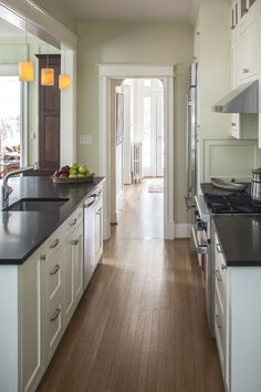 Galley kitchen with stone countertops and painted cabinets
