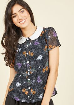 <p>Take a day to indulge in all the 'howl-iday' fun, wearing this black blouse! Featuring a smart white collar, pearly buttons, and clusters of pumpkins, bats, and boos, this sheer top captures the 'spirit' of the season wherever you go!</p>