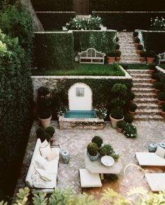 Mediterranean Exterior: An outdoor living area filled with patio furniture and potted boxwoods .