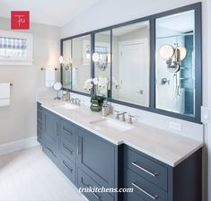This master bathroom boasts Wescott Navy painted cabinets from Grabill Cabinets in their Madison Square door style with beautifully framed vanity mirrors.