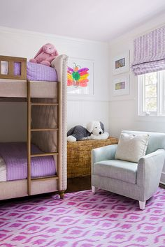 Chic purple girls' bedroom features upper walls painted white and lower walls clad in white beadboard trim lined with beige tufted upholstered bunk bed, Restoration Hardware Chesterfield Upholstered Bunk Bed, dressed in purple quilts.
