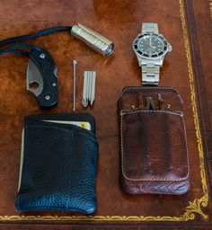 EDC Bladeart Mission Wallet containing: - Spyderco Dragonfly2- Swisscard Pen- Swisstech 4-in-1 screwdriver- cards & cash iPhone 4s in Ikonic Edge case (with eBay folding reading glasses)Lummi Raw NS 250/40 Lumen with green tritiumRolex Submarinersmall keyring with house and car key - not shown