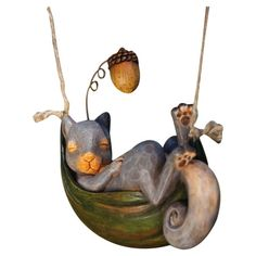 A whimsical addition to your garden or sunroom, this charming decor showcases a sleeping squirrel in a leaf hammock.  Product: Indoor...