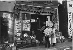 Picture of two men standing outside a fruit shop during the Great Depression.