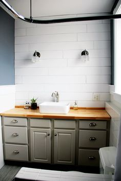 "Deciding our master bath wall needed a ""pop"" of interest, we did it up with plywood planks! The cheapest wall treatment aside from paint, it give our newly renovated master bath just the rustic look we were going for."
