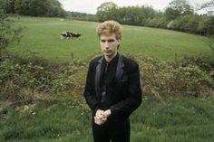 Nederlands zanger, tekstschrijver en componist FranK Boeijen (1957)  geheel in het zwart gekleed bij een weiland. Hij richtte de Frank Boeijen Groep op die successen boekte met Nederpop in de jaren tachtig van de twintigste eeuw. Nederland, ca. 1980.