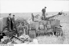 """s.Pz.Abt. 503, the men of the ammunition section take a break as the crew of Tiger 123 near the end of the ammunition loading process, Operation """"Zitadelle"""", July 1943."""