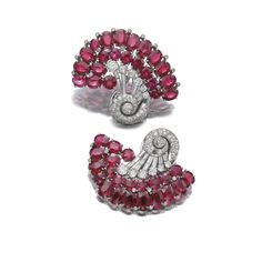 Pair of synthetic ruby and diamond clips, Seaman Schepps Each of scroll design, set with circular-cut and oval synthetic rubies, and circular-, single-cut and baguette diamonds, signed Seaman Schepps, clip fittings, a few diamonds deficient.