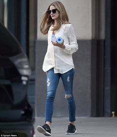 Stylish as always: Olivia looked gorgeous in a cream blouse, ripped jeans and trainers, after changing out of slip-on shoes