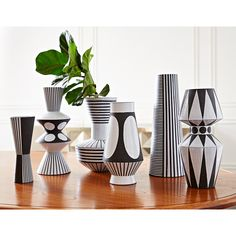 Couture Craft.Each one of the Palm Springs Vases is hand-thrown by skilled artisans in our Peruvian workshop. The vibe—crafty yet couture, graphic yet organic—is achieved through levels of rigorous craftsmanship.Thrown from black stoneware infused with chunky grog and trimmed and chattered* to create a striated texture. Patterns are masked off using tape and wax resist and finished with a satin-matte ivory glaze. Why not cluster three on a mantle or a bookshelf to create an haute hippie…