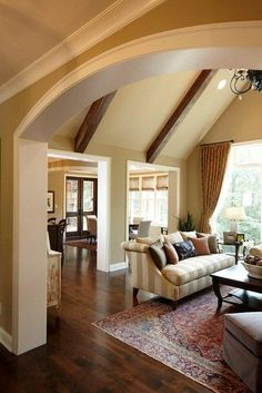 Love the archway from the foyer to the living room with the wood beams. Also like how living is separate from the kitchen, but still open.    paint color:  BM HC-79 Greenbriar Beige - walls   Paint OC-117 Simply White - casing