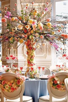 Silver birch branches burst with pink and cream blooms that also decorate the couple's chairs