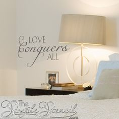 A custom vinyl romantic wall phrase, saying, quote that states Love Conquers All in an elegant scripted style perfect for your master bedroom decor.