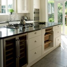 kitchen: grey floor tiles with black countertops, white cabinets