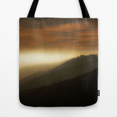 Mystical mountains Tote Bag by Pirmin Nohr - $22.00  Foggy day at the edge of the mountains, where they meet the plains. The light stripe is fog. On the mountain of the right side you see the silhouette of a huge castle ruin.   Nature, landscape, light, fog,sky, clouds, magical, dark, hazy, mist, misty