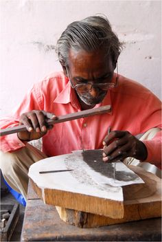 One of our skilled artisans in India meticulously carving and chiseling away at a wooden block to make beautiful blockprinted fabrics.