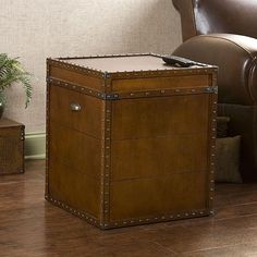 Crafted with a replicated antique look, this end table is ideal as a decorative accent and also serves as a trunk for convenient storage. The rich walnut finish is adorned with antique brass rivets along the trim for classic style.