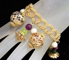 Mid Century gold tone costume beaded charm bracelet Faceted plastic beads with decorative gold tone filigree caps, and faux pearl beads 7 1/2 inches long, beaded charms average 1 inch Gold tone textured double link chain bracelet Fold over clasp Unsigned Good vintage condition, no wear to the metal, faceted smaller beads show minor wear, does not detract International buyers welcome, I can ship 3 jewelry items for 13.00 USD, over charges are automatically refunded prior to shipping Flat ...