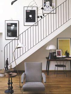 """Verrière, garde-corps, mobile de Calder (fondation Maeght), chaise du bureau (Asiatides) et piètement des guéridons : le métal noirci sert de fil conducteur. Dans l'escalier, des couvertures de Libé, Image Republic, surplombent le bureau """" Otsu """" en orme et noyer, Sodezign, éclairé par la lampe """" Pipistrello """", Martinelli Luce sur mondesign. com. Les sculptures de la maîtresse des lieux ponctuent l'espace."""