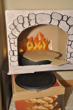 Cardboard pizza oven, sharpie & tempura paint, laminated tissue paper flames, free pizza boxes & cake pan bottoms.
