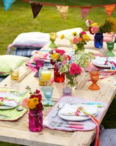 Lush colors of spring flowers and a gorgeous bunting make this outdoor picnic lunch so inviting. Almost a boho-gypsy style with a mix of colors and pattern. Love!