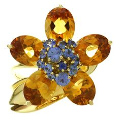 This stunning ring from Van Cleef & Arpels Hawaii collection is made in 18k yellow gold and features an open band accented with a leaf and a rotatable flower composed of 5 faceted citrine petals of an estimated 12.5 carats and a cluster of blue sapphires of an estimated 1 carat. Elegant and vibrant. Size 6, resizable, sizing fees will be provided upon request.