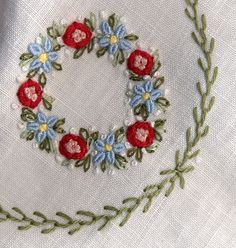 Close-up of cambric linen collar made by Trudy Horne. Embroidered wreath is composed of bullion and French knots, pinwheel flowers and lazy daisy stitches. Green garland is made using feather stitch.