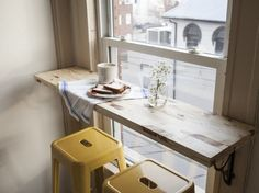 Transform a boring old window in an unused corner — just attach a wood plank and two stools for the cheeriest little breakfast nook.