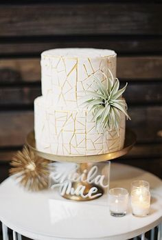 A two-tiered white-and-gold wedding cake with geometric details and decorated with an air plant by @daniellekeene15 | Brides.com
