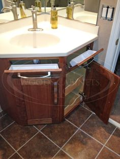 Cool corner bathroom vanity that utilizes space - pull-out drawers and pop-out tilt drawer (fold down front). Made of cherry wood by www.WoodsCabinets.com