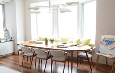 banc de cuisine le long de la fenêtre avec coussins jaune pastel, table et chaises en bois