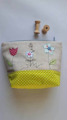 Flower applique zipped pouch/cosmetic case/toiletry bag/wash bag/pencil case is ideal as a storage bag for girls as well as a make-up bag/toiletry case for flower lovers with beautiful colours which immediatelly makes you think of spring or sunshine! Or it could also make perfect gift for coming Mothers Day. On the front there are 3 flowers with tiny butterfly appliqué on a plain oatmeal cotton/ linen fabric, with a coordinating bottom fabric and lining. Due to i...