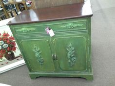 SOLD - This vintage wood cabinet has been painted a dark green, distressed and has rose bouquet applied to top drawer and cabinet doors. Dark wood tone top. New hardware.***** In Booth H12 at Main Street Antique Mall 7260 E Main St (east of Power RD on MAIN STREET) Mesa Az 85207 **** Open 7 days a week 10:00AM-5:30PM **** Call for more information 480 924 1122 **** We Accept cash, debit, VISA, Mastercard, Discover or American Express