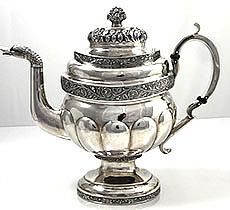 G Eoff Coin Silver Teapot -- An enormous American coin silver teapot in superb condition with hand chased decoration on a hand hammered surface. The spout has a duck head terminal and the finial is a basket of flowers. The manufacturer is Garrett Eoff, marked on the pedestal base. Active 1779 to 1845. Holds 10 cups. Small script monogram on one side only.