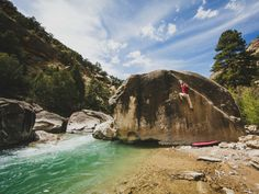 Bouldering in Joe's Valley is world class. Here a man climbs a boulder above the emerald waters of Cottonwood Creek, Utah
