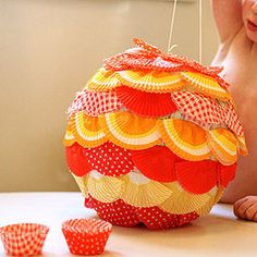 DIY pinata. This is for a basic ball shape (using a balloon as a base). You can paint or add decorations such as this pic of adding muffin liners. cute!
