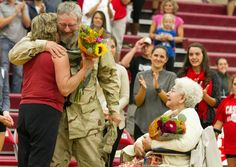 World photo/Mike Bonnicksen Marty Schmoker hugs his wife Sue as his mother Theresa, at right watches, smiling. Schmoker has been in Afghanistan for about a year and made a surprise visit home, showing up unannounced at the Cascade High School girls volleyball game Thursday.
