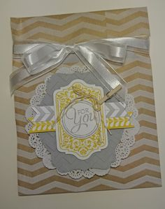 "Supplies include:  Tag a Bag bundle, Smoky Slate and Whisper White card stock, paper doily, Tape It and Chalk Talk stamp sets,  Smoky Slate and Crushed Curry ink, Deco Labels and Chalk Talk framelits,  5/8"" Organza Ribbon."