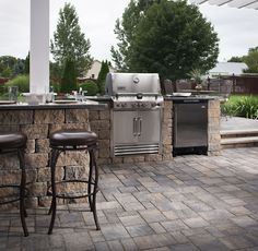 Outdoor kitchen and grilling area featuring a bar height counter and stools. #UrbanaPaver #CeltikWall