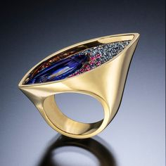 Plumé Vibrante Ring is daring and exotic. This ring features a tanzanite accented by magenta rubies and purple and blue sapphires set in yellow gold.