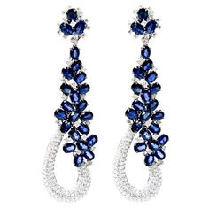 This gorgeous pair of Goldiva earrings in 18k white, designed by Diana M. , feature flower design blue sapphires, of exquisite color, weighing 26.10 carats total with 7.01 Carat of round brilliant cut white diamonds of D-E color, VS clarity and excellent cut and brilliance.These earrings contain posts and push backs. The earrings measure 13.5mm in length and 12mm at the widest point. 21st Centuty