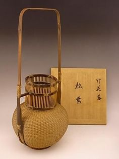 "Japanese 20th century bamboo flower basket by basket master, OKADA SESSAI. OKADA SESSAI was a student of IIZUKA ROKANSAI. The basket measures 19"" tall by 8 1/2"" in width and 8"" in depth. Comes with TOMOBAKO, or original artist signed wooden storage basket"